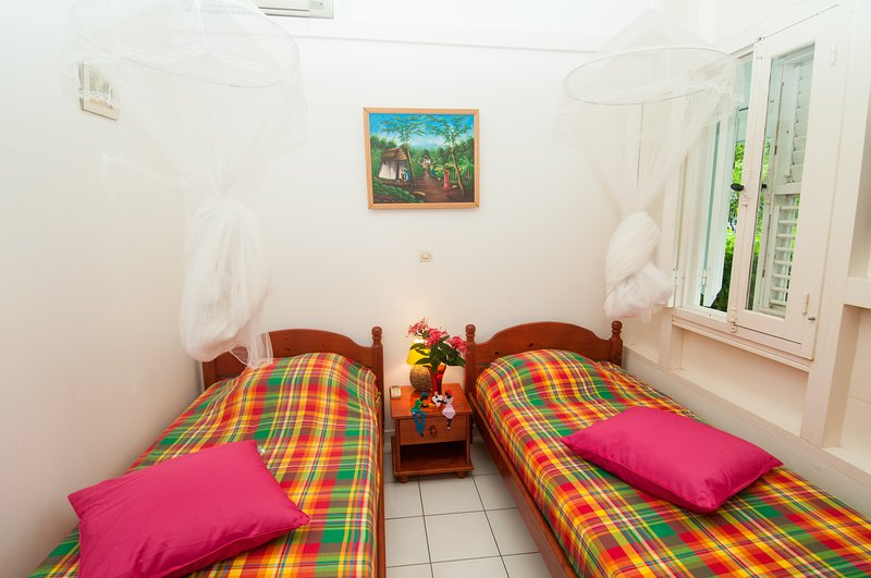 room with 2 beds, air conditioning and mosquito nets, garden window, closet.