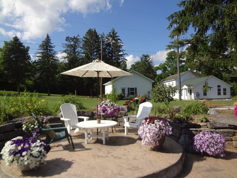 Raised patio area, with table, chairs and umbrella