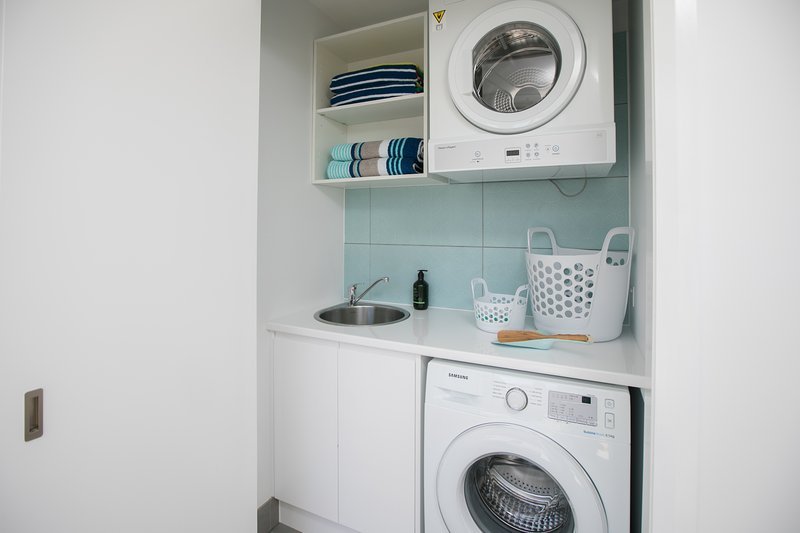 Laundry, with washer, dryer, sink, outdoor clothes line, iron & ironing board & beach towels.
