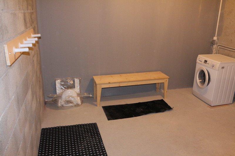 El garaje con perchas de arranque y la máquina de lavar