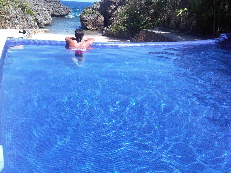 piscina con vistas a la playa privada que lleva al océano