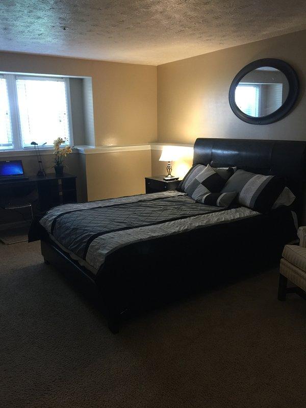 Dormitorio principal con cama doble engañoso anuncio de estación de trabajo