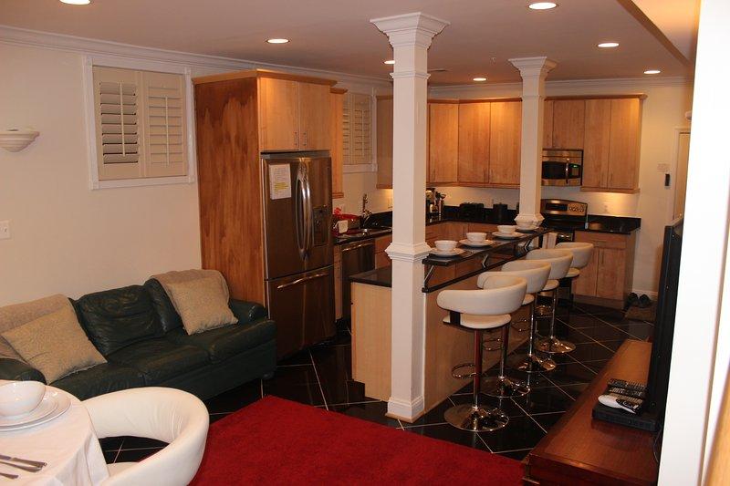 bela cozinha e sala de jantar com tampo de granito, bar, banqueta e mesa e cadeiras para refeições