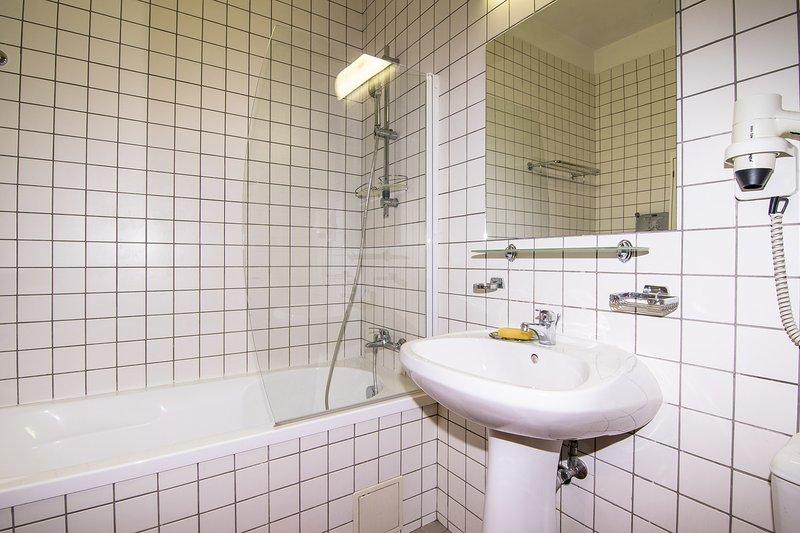 Salle de bains spacieuse avec baignoire