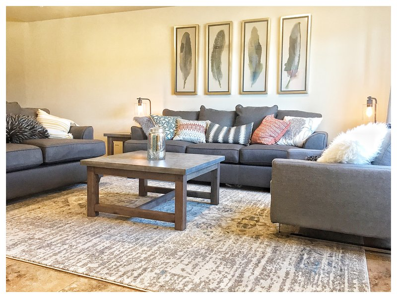 Front room with full size memory foam sofa sleeper and 60' smart TV
