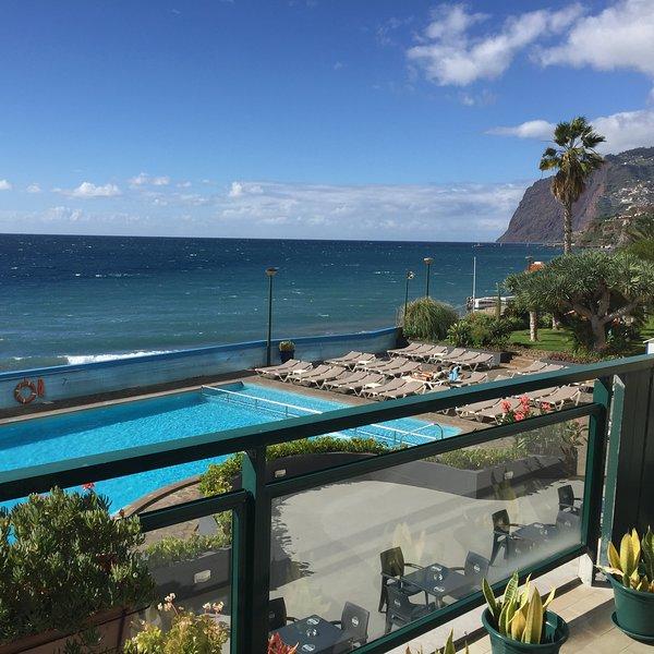 Balcón con vistas a la piscina y playa.