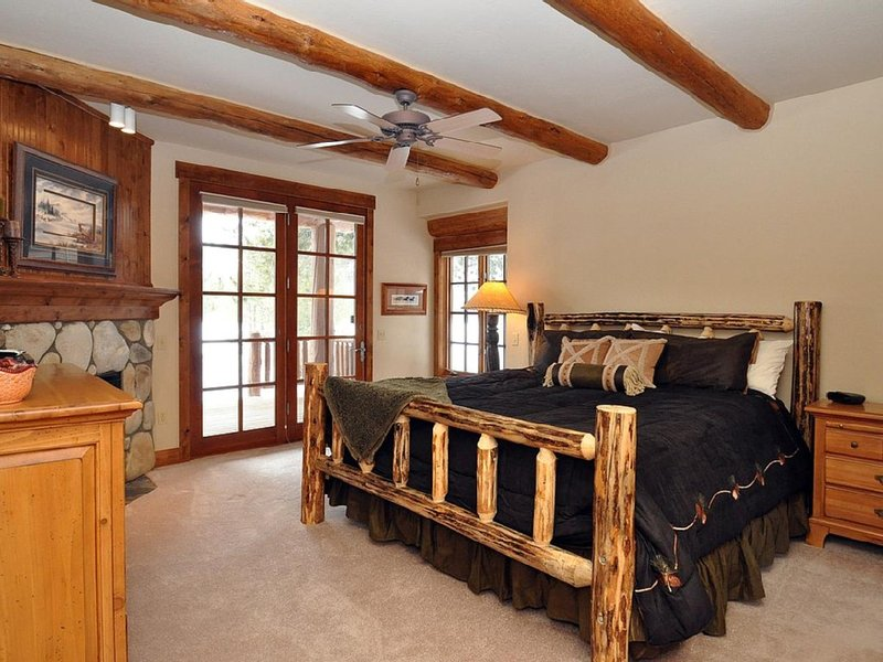 Master Bedroom with King Bed, fireplace, walkout doors to patio, and ensuite bath with Jacuzzi tub