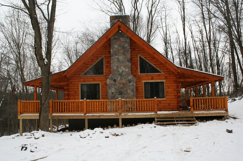 A peaceful cabin nestled in the woods, large decks on 3 sides.