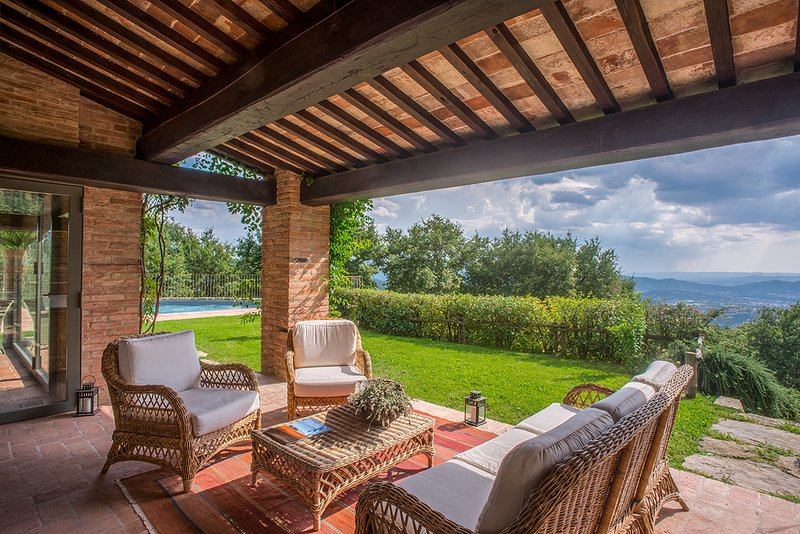 Villa Mandorlo's covered patio with panoramic view on the valley, Arezzo and the Tuscan hills