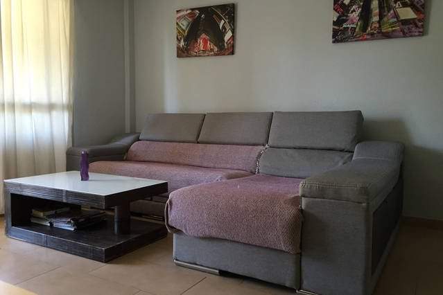 Salon - dining room has a sofa, TV, dining table. Very bright with balcony exit