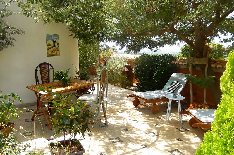 Front garden terrace with breakfast table and sunbeds