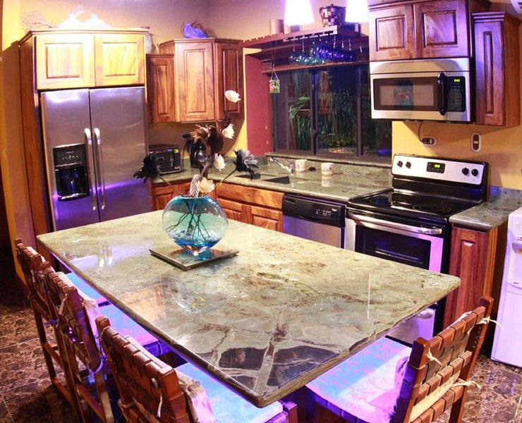 Kitchen with imported exotic Argentine granite counters, and custom rainforest wood.