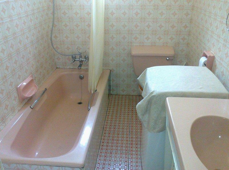 Banheiro com banheira chuveiro e máquina de lavar roupa