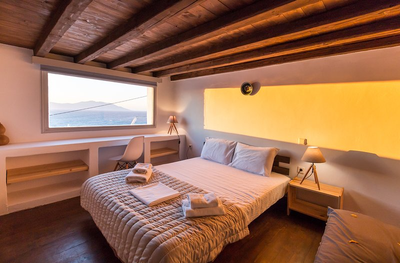 The bedroom at the mezzanine floor offers the greatest views of the Mykonian golden sunset