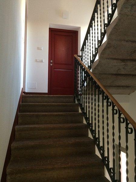 Scala piedra roja Trento con puerta de entrada al apartamento