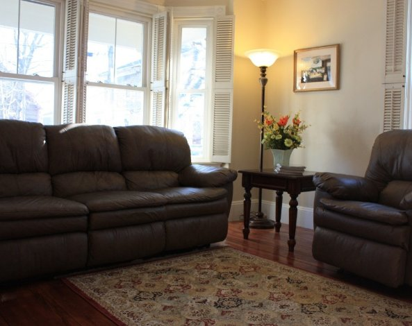 Front room with reclining chair and reclining sofa, large flat screen TV.