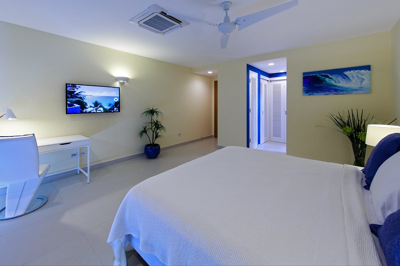 Master bedroom is designed in white and blue, upgraded with decorative plants