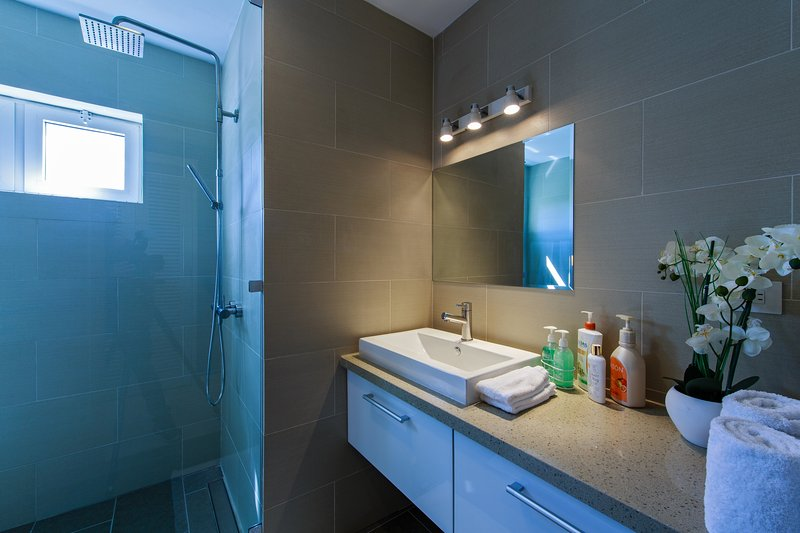 Each bedroom has a clean and modern bathroom equipped with shampoo, lotion and soaps
