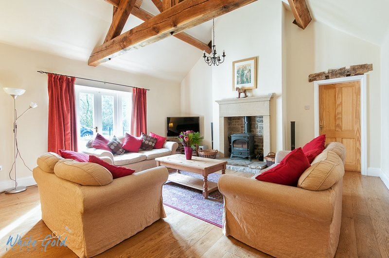 Large lounge with exposed beams, log burner, wooden floors, surround sound TV