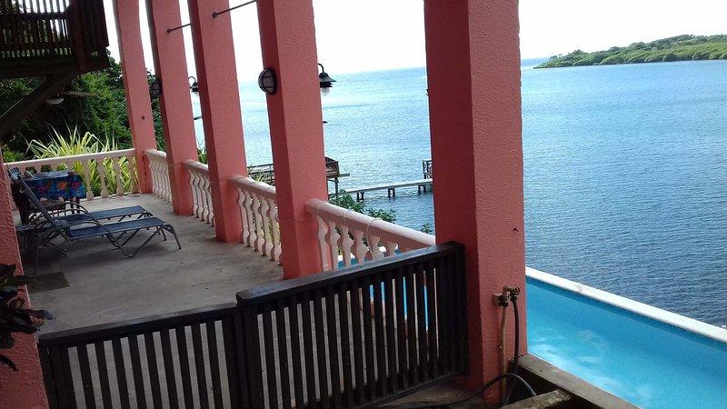 Su terraza privada con vistas a la piscina y al mar.