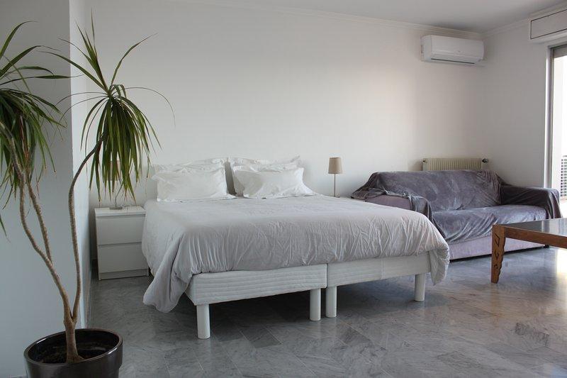 Main room met een tweepersoonsbed en een bank, een toegang tot het terras en uitzicht op zee