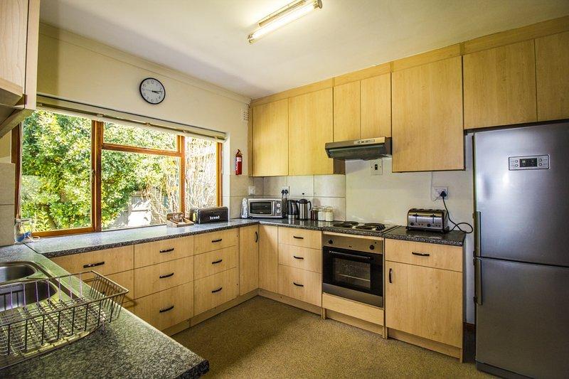 cuisine Maison principale entièrement équipée avec plaques de cuisson et four, frigo-congélateur, micro-ondes et lave-vaisselle