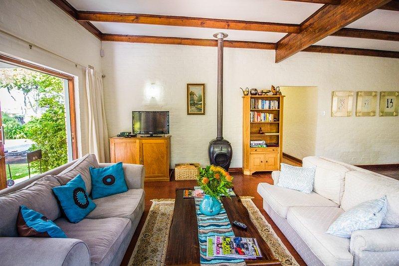 salon Maison principale avec cheminée, TV, cheminée et une petite bibliothèque
