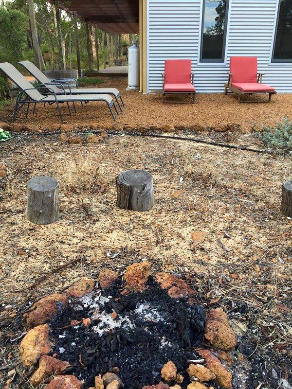 Sentar e assistir os marshmallows crianças brinde ao redor do fogo-pit.