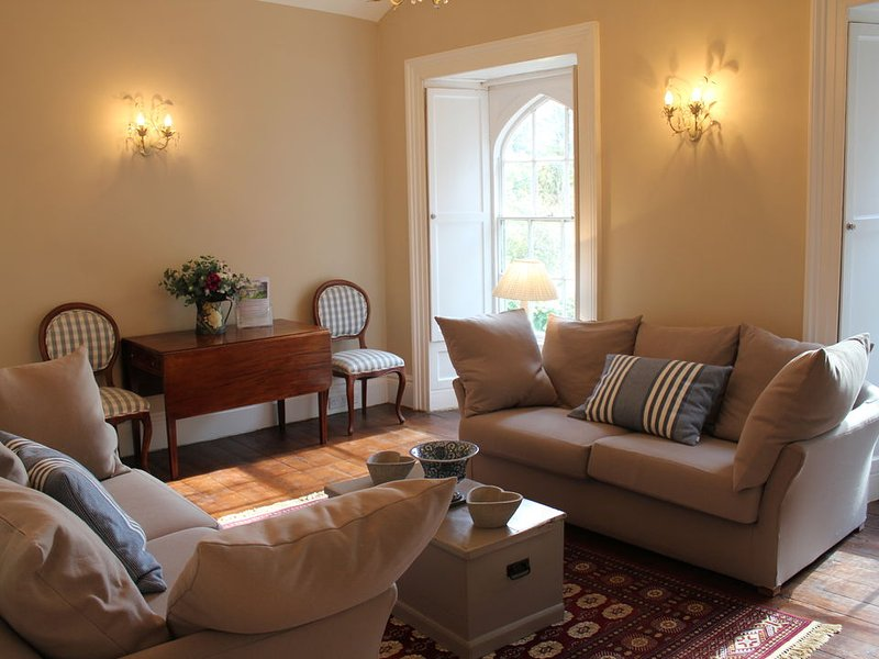 The sitting room has arched windows overlooking the gardens