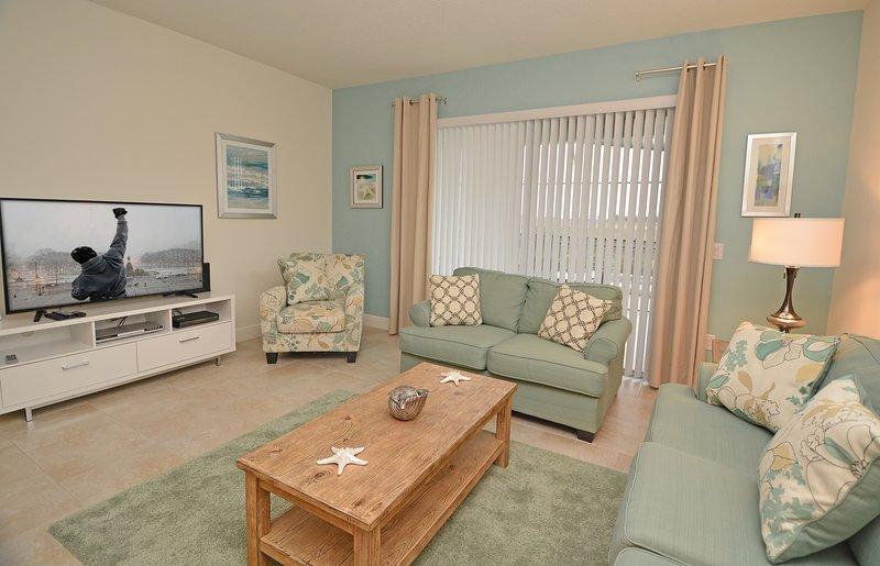 Área de asientos familiares con pantalla plana y puertas de patio