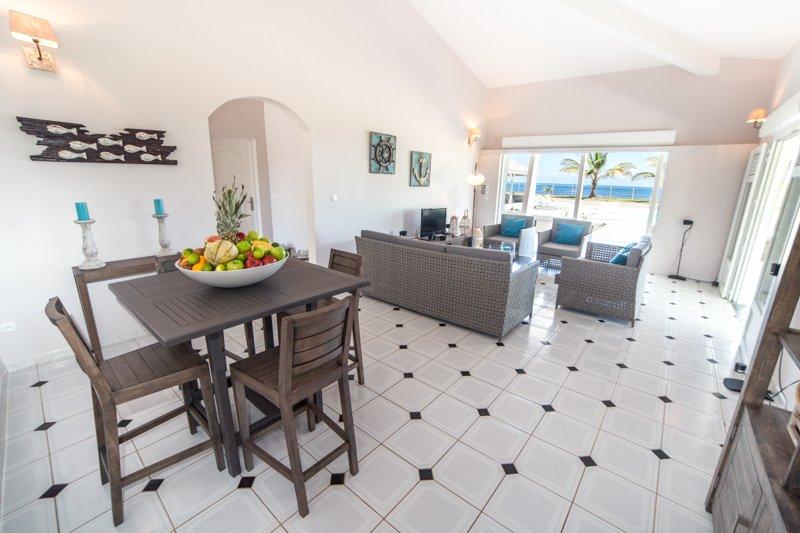 En la continuación de la cocina, una mesa auxiliar y un salón