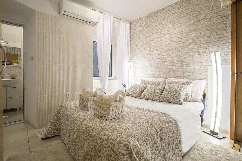 Camera da letto moderna luminosa, con letto matrimoniale e aria condizionata