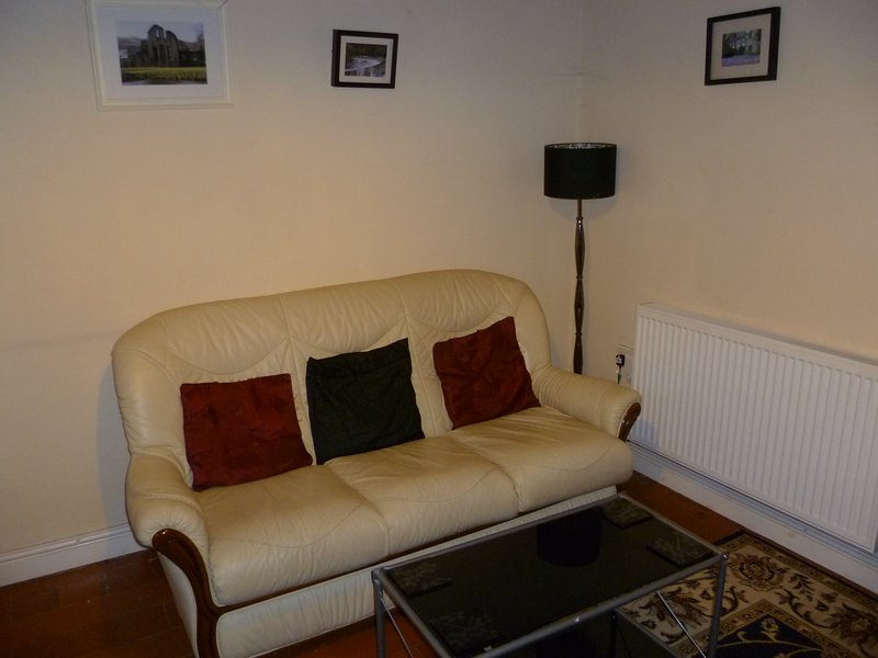 Large three seater faux leather sofa in the lounge