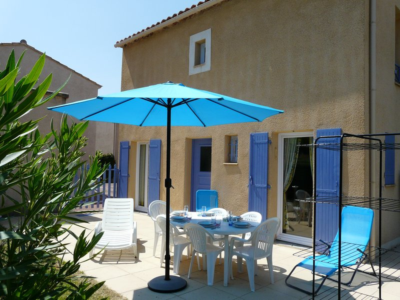 the house and terrace with garden furniture, folding chair to the pool