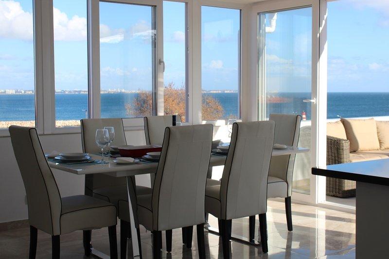 Americana de estar, cocina y comedor mirando por encima de las paredes de la ciudad al mar punto de vista real.