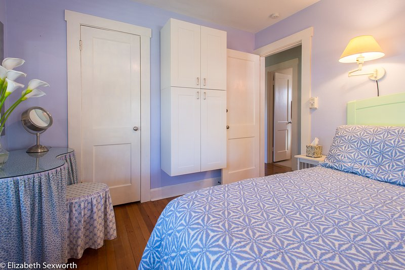 Master bedroom has queen bed, mounted cabinets, vanity, closet, TV, dresser, Annie Selkie linens