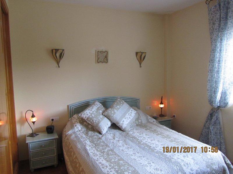 Dormitorio principal con baño privado, aire acondicionado, ventilador de techo y unas vistas preciosas de las montañas en la espalda