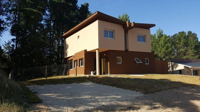 sud west facade, parking place, the perimeter fence of the lot and the pine forest is