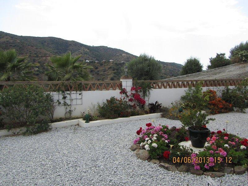 Jardín frontal de Villa con macizos de flores coloridas