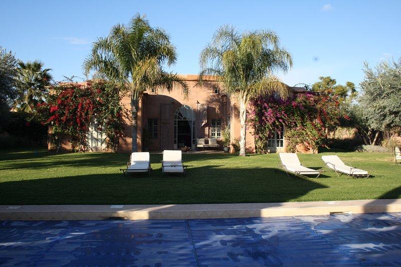 Zwembad en prachtige tuin met villa op de achtergrond
