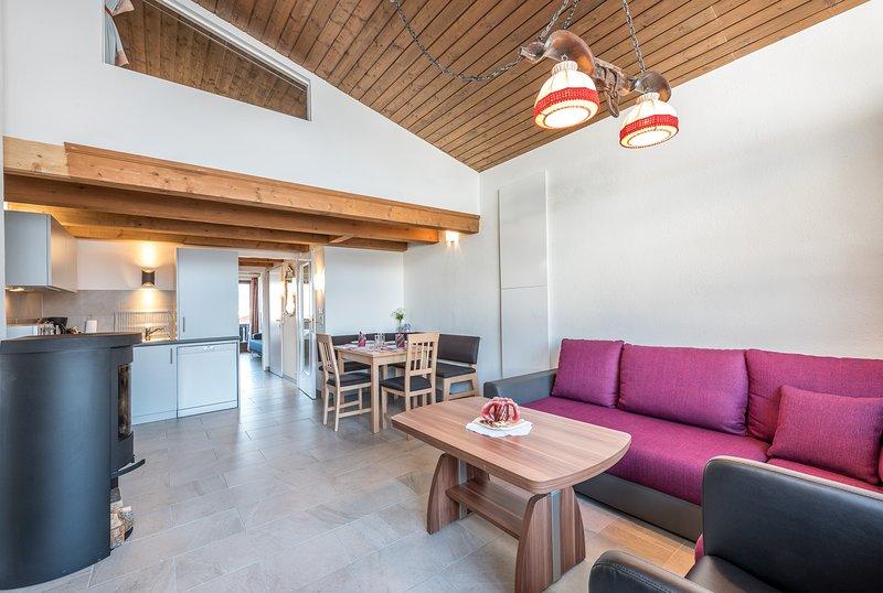 Das Wohnzimmer mit Holzofen, voll ausgestattete Küche, Essecke und bequemes Sofas.