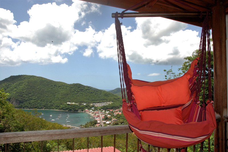 Your hammock is an observatory over the village of Deshaies, sea and boats