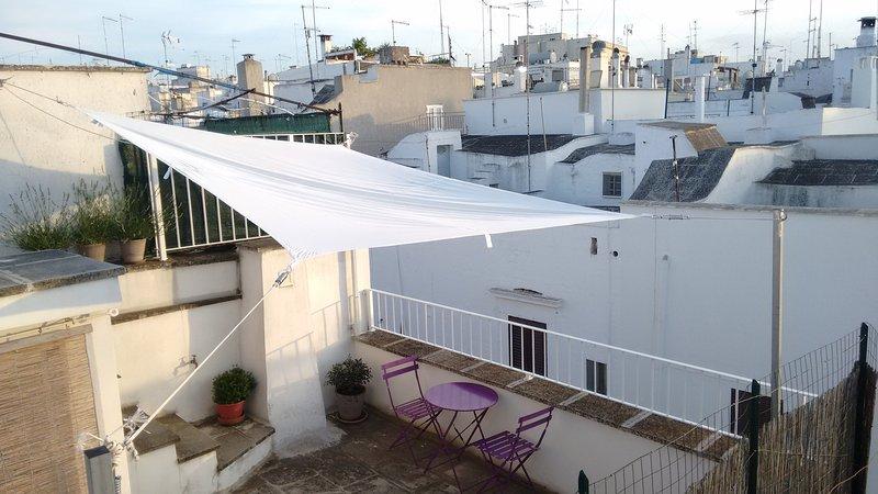 La terraza tiene una vista de las casas blancas de Ostuni ...