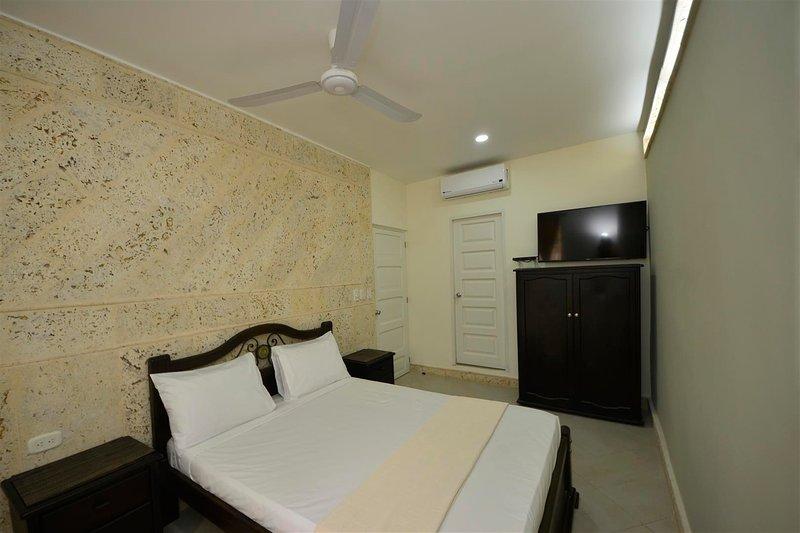 Chambre avec porte de salle de bains et porte sur séjour en arrière-plan