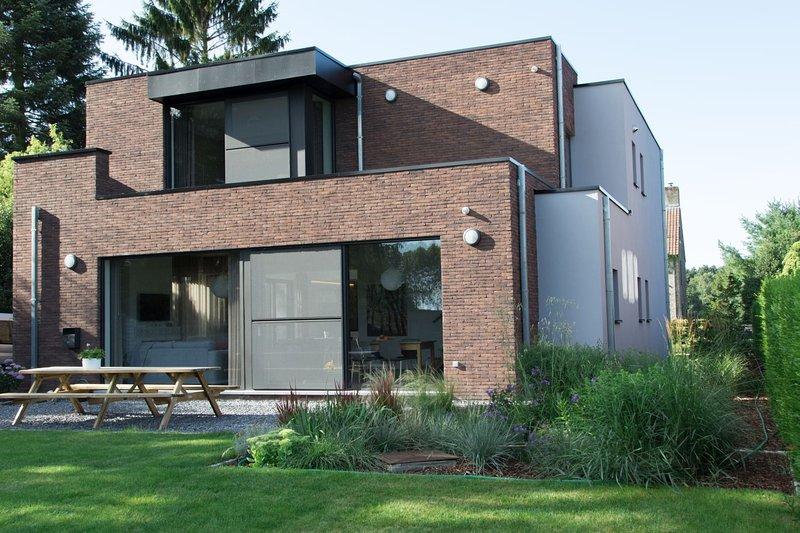 De gevel aan de tuinzijde.  een moderne uitstraling met grote ramen met zicht op tuin en landschap.