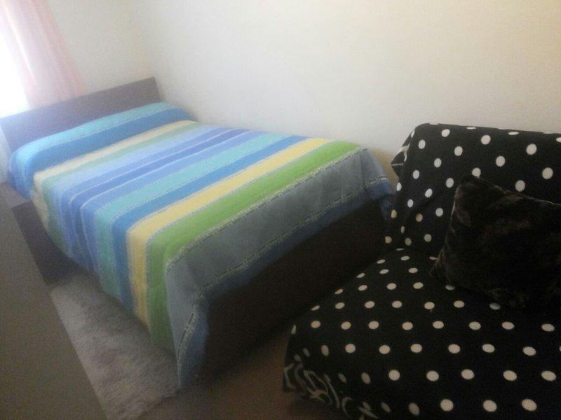 Un lit dans la deuxième chambre et un canapé-lit, moquette et placard pour les vêtements.