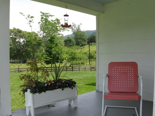 From this end of the porch, enjoy the mountains, stream and hummingbirds in front of you.