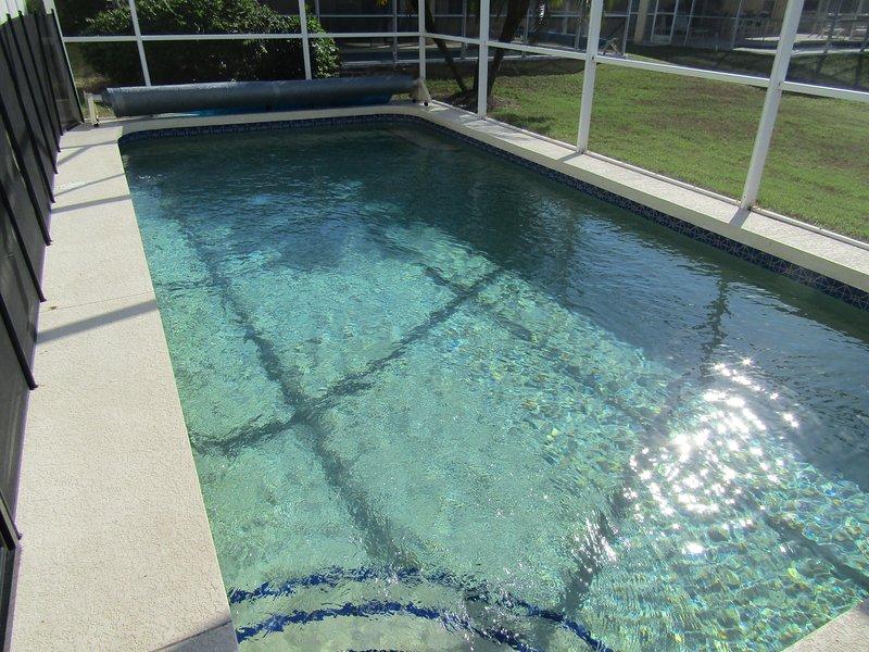 Uppvärmd pool med lock och undervattensbelysning för kvällen simmar.