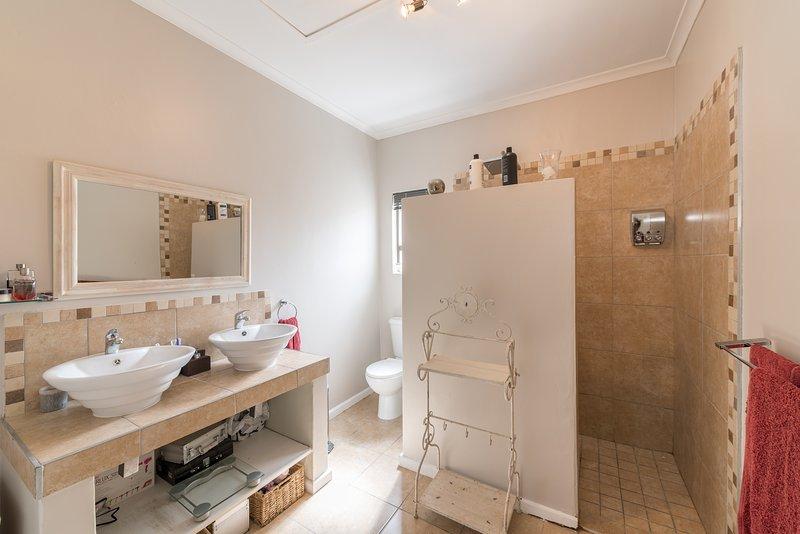 La salle de bains familiale dispose d'une grande douche, une baignoire et une double vasque.