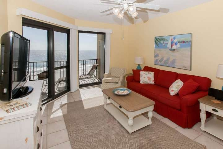 Tiled living room with seating for 5, ceiling fan and Gulf-front balcony access